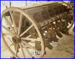 Two vintage 1920s large 4ft 5 inches tall wood wagon wheels on Smyth seed drill